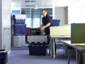 movers packing Stevens crates in office